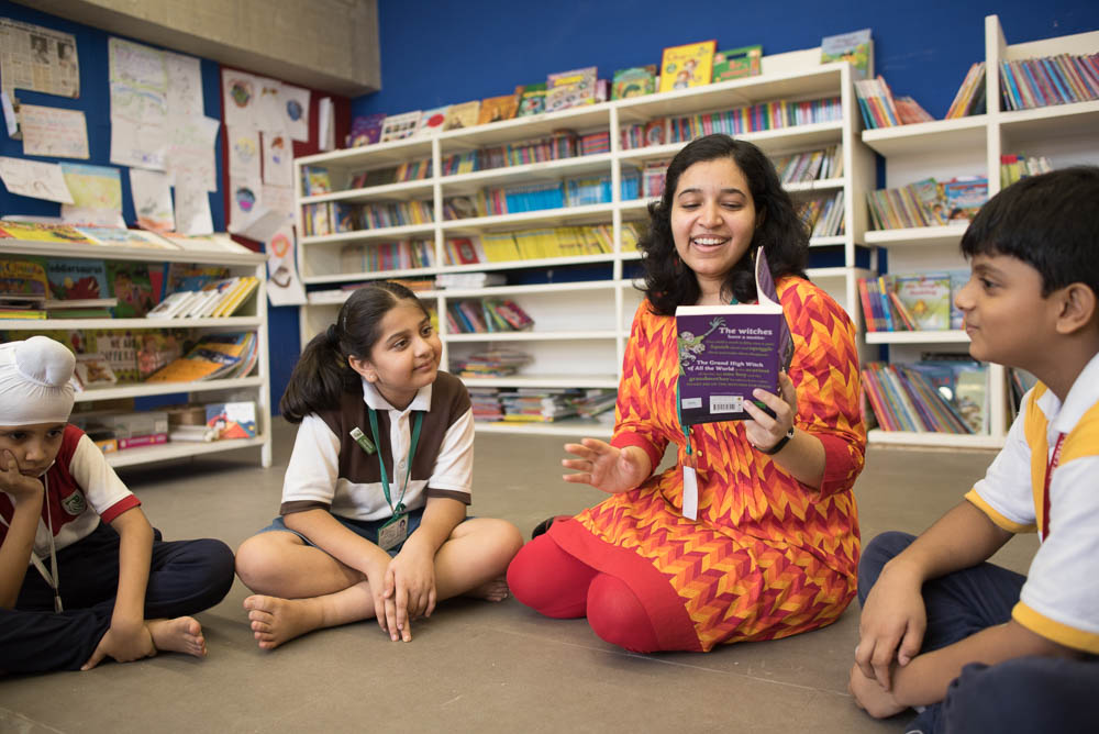 A teacher reading a book to kids in library at The Green Acres Academy